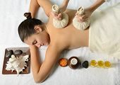 portrait of young beautiful woman in spa environment, massage with spa herbal balls