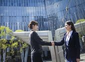 Two smiling young businesswomen shaking hands outdoors