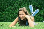 Smiling teenager laying down in a grass in a park