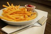 French fries with salt and ketchup in a plate with fork on white napkins