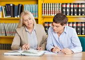 Mature female teacher explaining student while sitting at table in university library