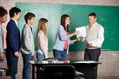 Mature male teacher giving test result to student while classmates standing in row at classroom