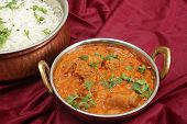 Lamb rogan josh, served with jeera (cumin) rice in beaten copper bowls. A tilt-shift lens has been u