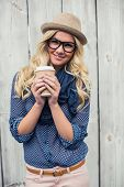 stock photo of wooden fence  - Happy trendy blonde holding coffee outdoors on wooden background - JPG
