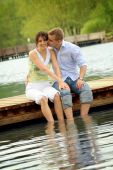 Couple Sitting On A Bridge In Front Of A Lake