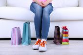 Woman sit on sofa with bags of shopping close-up