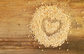 Sesame seeds in a shape of heart isolated on wooden background