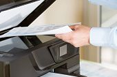 stock photo of peripherals  - Performing a photocopy clerk with multifunction printer