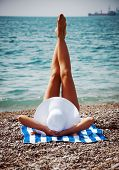 Seductive woman taking sunbathe on beach