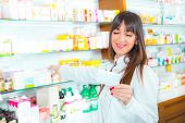Portrait of a smiling female pharmacist with prescription in front of medicines at drugstore