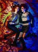 image of inverted  - Fashion portrait of two girls in glam rock style lying on colorful background - JPG