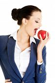 Young business woman with red apple. Isolated on white.