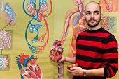 Biology teacher shows human heart model