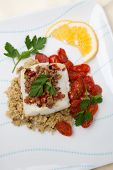 image of halibut  - Baked halibut with olive tapenade crust garnished with couscous fried cherry tomatoes and fresh parsley - JPG