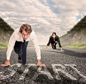 stock photo of kneeling  - man versus woman on a road ready to run - JPG