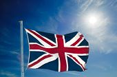 Union Jack flying high, against blue sky with copy space