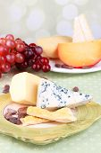 Assorted cheese plate , grape, bread sticks.  on table, on light background