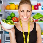 Closeup portrait of beautiful cheerful girl holding in hand bowl with fresh tasty green salad, dieti