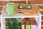 Composition with glasses and books, on cabinet, on color wall background