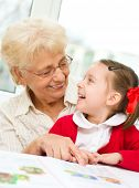 stock photo of grandmother  - Grandmother teaches to read a book her granddaughter - JPG