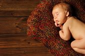 Baby Newborn Portrait, Kid Sleeping In Woolen Blanket On Brown Wooden Background