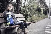 picture of school bullying  - Little girl coming from school sitting lonely at a bench outdoors - JPG