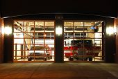 stock photo of firehouse  - Modern fire station at night with fire apparatus - JPG