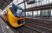 stock photo of passenger train  - Yellow train stands on the central railroad station in Amsterdam - JPG