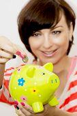 Young Woman Gives A Euro Coin Into Decorative Ceramic Piggy Bank