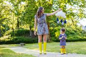 Mother And Little Adorable Child In Yellow Rubber Boots