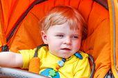 Lovely Toddler Boy Smiling Outdoor In Orange Stroller