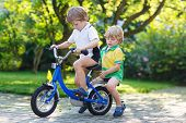 Two Happy Little Sibling Kids Having Fun Together On One Bicycle