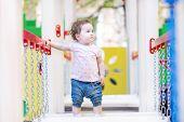 Sweet Little Girl Climbing On A Playground