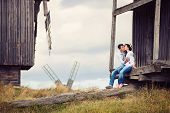 Young couple kissing on steps of old windmill
