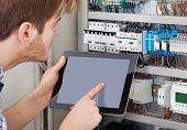 Technician Examining Fusebox Using Tablet