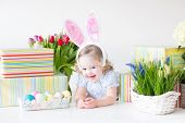 Happy Toddler Girl in Bunny Ears With Easter presents