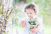 Beautiful Curly Toddler Girl holding first spring flowers in a transparent crystal vase