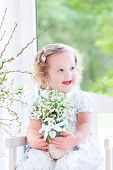 Beautiful Curly Toddler Girl In A White Dress Sitting In A White Rocking Chair