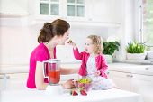 Happy Toddler Girl And Her Young Mother Making Fresh Strawberry And Other Fruit