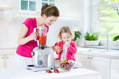 Laughing Toddler Girl And Her Beautiful Young Mother Making Fresh Strawberry And Other Fruit