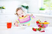 Beautiful Toddler Girl having breakfast drinking juice and eating corn flakes with strawberry