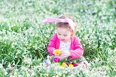 Beautiful Toddler Girl Wearing Bunny Ears Playing With Easter Eggs In A White Basket