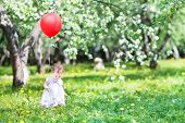 Beautiful Little Girl Playing With A Red Balloon In An Apple Tree Garden
