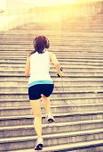 Runner athlete running on city stairs. woman fitness jogging workout wellness concept.