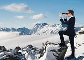 Businessman Looking Through Handheld Telescope In Snow