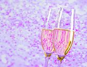 Champagne Flutes With Gold Bubbles On Blur Violet Tint Light Background