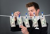 Businessman Drying Dollar Bills On Clothesline