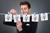 Businessman Pinning Papers Lightbulbs On Clothesline