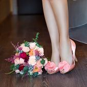 Female Feet In Pink Wedding Sandals With A Wedding Bouquet