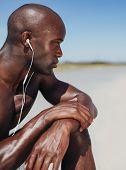African Man Wearing Earphones Sitting Alone